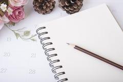Crayon de plan rapproché sur le journal intime de carnet avec le calendrier et la fleur rose Photo stock