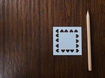 Crayon en bois brun naturel et papier blanc de place blanche qui a été poinçonné dans la forme de coeur Photos libres de droits