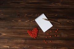 Crayon en bois sur le carnet ouvert et ashberry rouge comme forme de coeur à la table Photos stock