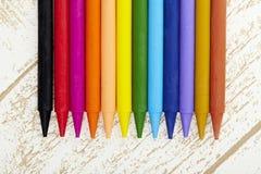 Crayon en pastel de douze couleurs dans la fin de cadre vers le haut avec le backgrou boisé de texture Images libres de droits