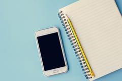 Crayon et bloc-notes futés de téléphone sur le bleu Images libres de droits