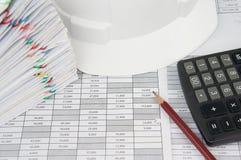 Crayon et calculatrice avec le chapeau et le document blancs d'ingénieur de tache floue Images libres de droits