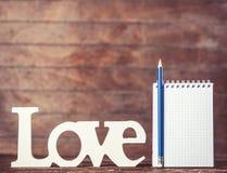 Crayon et carnet avec amour de mot Photo libre de droits