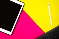 Crayon et clavier de Tablette sur le ton du fond deux avec l'espace jaune et rose de copie photographie stock