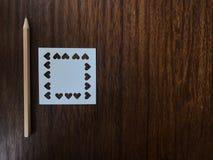 Crayon et livre blanc qui a été poinçonné dans la forme de coeur sur la table Photos libres de droits