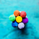 Crayon flower on blue. Rainbow crayon flower shape on blue background Stock Photo