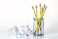 crayon jaune d'or dans le pot en verre avec le papier chiffonné dessus Image libre de droits