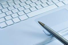 Crayon lecteur argenté sur un clavier d'ordinateur portatif Photo stock