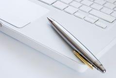 Crayon lecteur argenté sur un clavier d'ordinateur portatif Photographie stock libre de droits