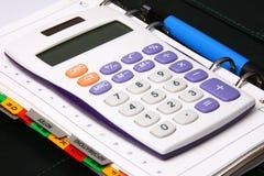 Crayon lecteur bleu, calculatrice blanche sur un organisateur vert Photos stock