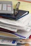 Crayon lecteur, calculatrice et chéquier sur une pile de factures Images libres de droits