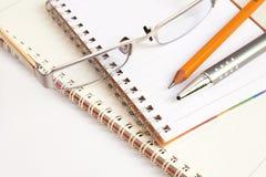 Crayon lecteur en verre de cahier et crayon jaune sur le Ba blanc Images libres de droits