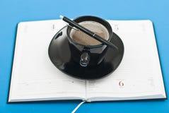 Crayon lecteur et ordre du jour de cuvette de café Photo stock