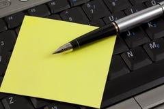 Crayon lecteur et post-it sur un ordinateur portatif Photos stock