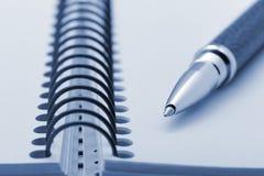Crayon lecteur et un cahier sur une spirale avec un papier jaune Photographie stock libre de droits