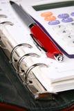 Crayon lecteur rouge et calculatrice blanche sur un organisateur vert Photo stock