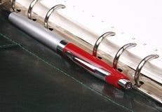 Crayon lecteur rouge se trouvant sur un organisateur en cuir vert Photographie stock