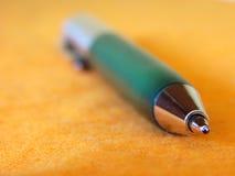 Crayon lecteur vert sur l'orange Photos stock