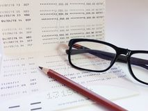 Crayon, lunettes et carnet de compte d'épargne d'épargnes ou relevé de compte financier sur le fond blanc photographie stock