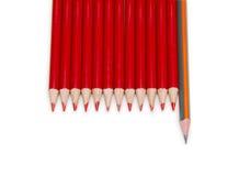 Crayon noir se tenant des crayons de rouge, d'isolement Images stock