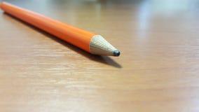 Crayon orange sur le bureau en bois Photographie stock