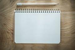 Crayon ouvert de bloc-notes sur le conseil en bois Image libre de droits