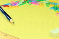 Crayon, règle, gomme, trombones sur le papier Photographie stock