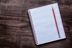Crayon rouge et bloc-notes carré sur le pin en bois Image stock