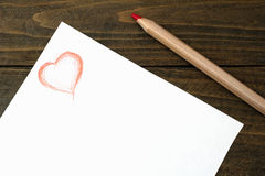Crayon rouge et coeur dessinés Photographie stock