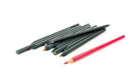 Crayon rouge et crayons noirs sur le fond blanc Photo libre de droits