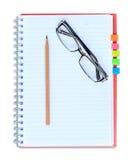 Crayon rouge et lunettes de carnet d'isolement sur le fond blanc Photo stock