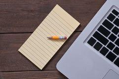 Crayon sur le bloc-notes et l'ordinateur Photographie stock libre de droits
