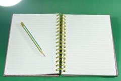 Crayon sur le carnet de notes à spirale et les livres images stock