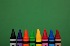 Crayon tops with a green chalkboard background Stock Photography