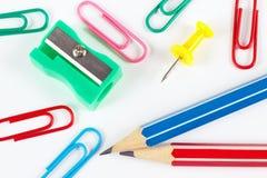 Crayon, trombones, affûteuse et punaise sur le plan rapproché de bureau blanc Images libres de droits