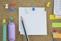 Crayonnez avec les notes, la goupille, la clé et le nom collants d'étiquette sur le panneau de liège Photographie stock libre de droits