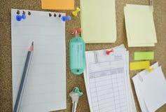 Crayonnez avec les notes, la goupille, la clé et le nom collants d'étiquette sur le panneau de liège Images stock