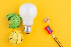 Crayonnez, chiffonnez le papier et l'ampoule au-dessus du fond jaune photo stock