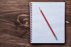 Crayonnez et avez ajusté le bloc-notes sur le brun de pin en bois Photos stock