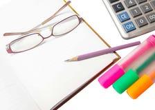 Crayonnez sur un journal intime avec des verres, des stylos, des barres de mise en valeur et un calcul Image stock