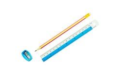 Crayonnez, taille-crayons et règle sur le fond blanc Photographie stock libre de droits