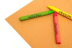 Crayons воска на бумаге ремесла на белой предпосылке Стоковое Изображение RF