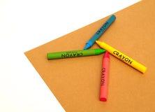 Crayons воска на бумаге ремесла на белой предпосылке Стоковая Фотография