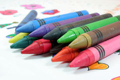 Crayons. Bunch of crayons over a child's drawing Royalty Free Stock Photo