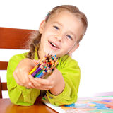 Crayons. Sitting young girl with crayons Stock Image