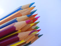 Crayons against a blue sky. Lots of coloured crayons set against a blue sky Royalty Free Stock Image