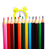 Crayons and alarm clock. In background as concept for school time Royalty Free Stock Photos