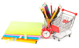 Crayons and alarm clock with shopping cart Royalty Free Stock Photo