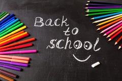 Crayons aux cercles et au titre de nouveau à l'école écrite sur les morceaux de papier jaunes sur le tableau noir d'école Photo libre de droits