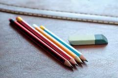 Crayons avec la gomme d'isolement sur le fond en cuir Foc sélectionné Photographie stock